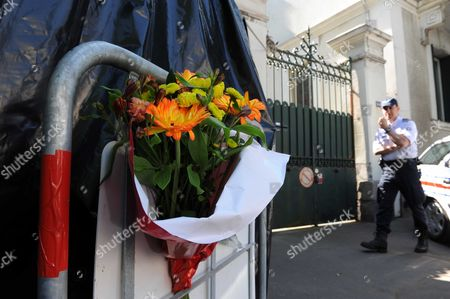 A police officer and flowers outside the house where the bodies were found