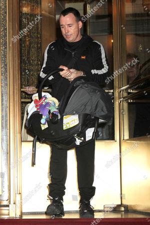 David Furnish carrying his son Zachary Jackson Levon Furnish John, and Sir Elton John