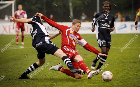 Stock Image of Juho Merilainen (L) and Dominic Yobe (R) of AC Oulu stop Justus Vajanne of FC Viikingit during the Finnish first division football match between FC Viikingit and AC Oulu in Helsinki
