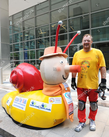Lloyd Scott completing the London marathon dressed in a giant Brian the Snail costume that requires him to drag himself along the ground with nothing but his hands