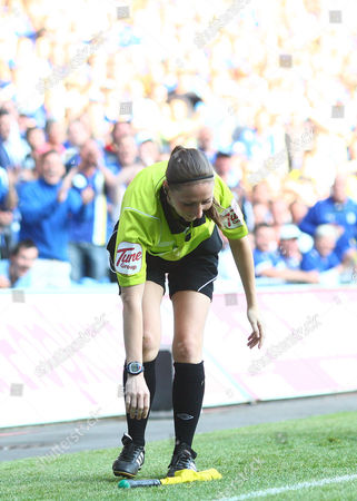 Assistant referee Sian Massey picks up her flag after falling over