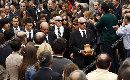 Baldomero Ballesteros carries the urn containing the ashes of his brother Severiano Ballesteros