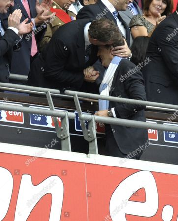Manchester City Chief Executive Garry Cook hugs Manchester City manager Roberto Mancini