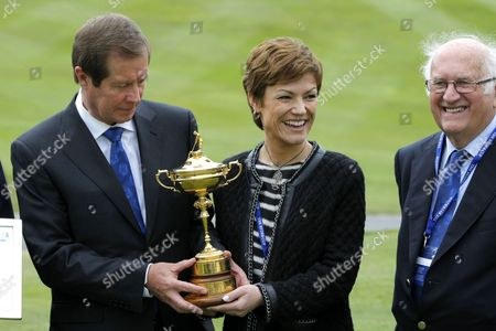 George O'Grady (Executive Director of the European Tour) inspects the Ryder Cup trophy with Chantal Jouanno, France's Minister of Sport, as Neil Coles (Chair of the European Tour) looks on