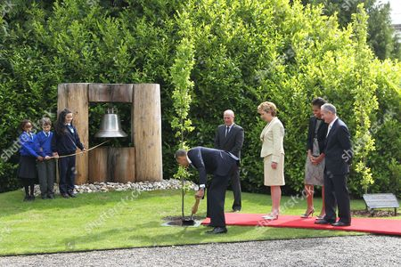 Schoolchildren Onyedika Ukachukwu, Colm Dunne and Maragaret McDonagh at the Peace Bell, as President Barack Obama plants a tree watched by Robert Norris, Head Gardener; President of Ireland Mary McAleese, First Lady Michelle Obama, and Dr Martin McAleese at Aras an Uachtarain, Dublin