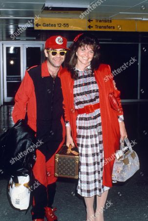 ELTON JOHN AND WIFE RENATE BLAUEL AT HEATHROW AIRPORT, LONDON