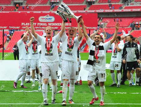 Alan Tate , Garry Monk and Leon Britton of Swansea celebrate promotion with the trophy
