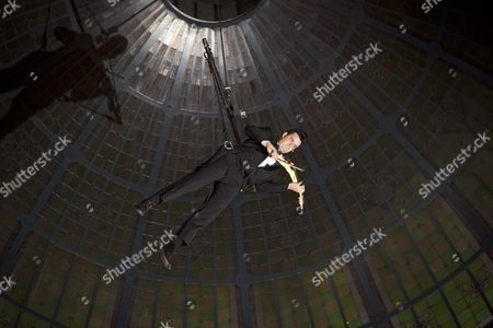 Editorial image of Aerial violinist Shenzo Gregorio performs while suspended under the Queen Victoria Building Dome, Sydney, Australia - 16 Jun 2011