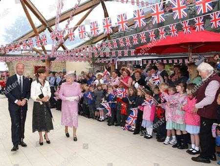 Alan Shearer, the Duchess of Northumberland and Queen Elizabeth II walking past a group of schoolchildren