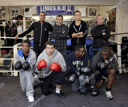 Boxers, James DeGale (back left), Kevin Mitchell (rear 2nd from left) and JJ Bird (rear 2nd from right) pose for a group shot with teenagers after a coaching session run in an Islington gym by Team Olympics
