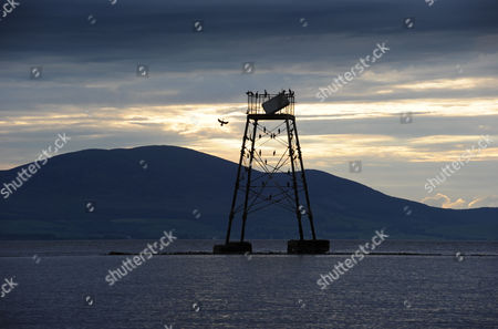 Stock Photo of Cormorants roost on the channel marker known as 'Jenny-Long-Legs', Silloth Harbour, Cumbria, Britain - behind can be seen Criffel Mountain across the Solway Firth near Dumfries in south west Scotland