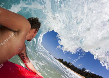 Stock Image of Ray Collins inside the barrel of a wave on his bodyboard near his home in Woolagong