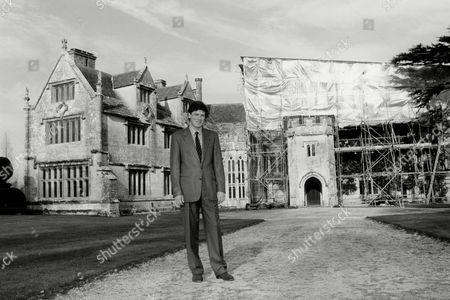 Athelhampton Manor. Patrick Cooke Outside One Of The Wings Undamaged By The Fire. Athelhampton Is One Of The Finest 15th-century Manor-houses And Is Surrounded By One Of The Great Architectural Gardens Of England. The House Contains Many Finely Furnished Rooms Including The Great Hall Great Chamber Wine Cellar. The Gallery In The West Wing Exhibits Works By The Russian Artist Marevna Who Lived At The House In The 1940s/50s. The Grade I Listed Garden Dating From C1891 Is Full Of Vistas And Gains Much From The Fountains And River Piddle Flowing Through. The Walled Gardens Include The World-famous Topiary Pyramids And Collections Of Tulips Roses Magnolias Clematis And Lilies. Also 15th-century Dovecote And Boardwalk Along The Banks Of The River Piddle. Winner Of 1997 Christies' Garden Of The Year Competition.
