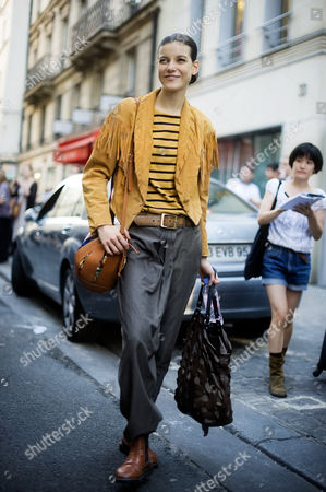 Model Tati Cotliar photographed on the streets of Paris, wearing a suede leather jacket, and grey harem pants.