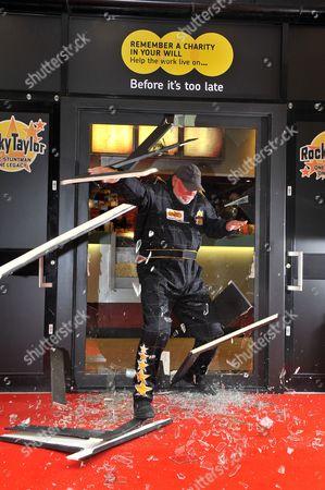 Rocky Taylor jumping through a sugar glass door frame
