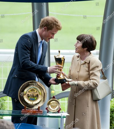 Prince Harry presents the King George the VI trophy to the winning owner Lady Serena Rothschild