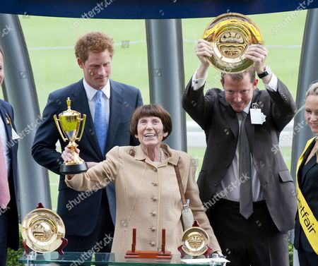 Stock Image of Prince Harry presents the King George the VI trophy to the winning owner Lady Serena Rothschild and guest