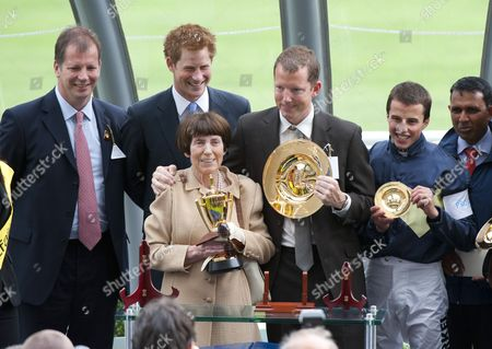 Prince Harry presents the King George the VI trophy to the winning owner Lady Serena Rothschild and guest and the winning jockey