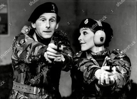 Actors Patricia Hodge And Christopher Godwin In Army Camouflage And Handguns Filming Comedy Holding The Fort 1981.