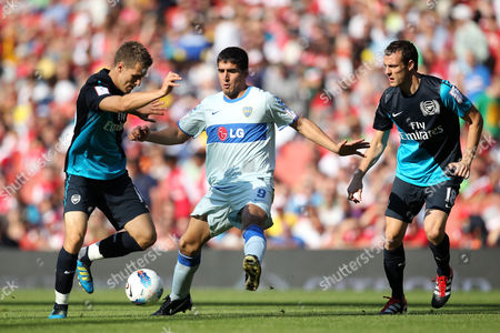 Aaron Ramsey (L) and Sebastien Squillaci of Arsenal tangle with Lucas Viatri of Boca Juniors