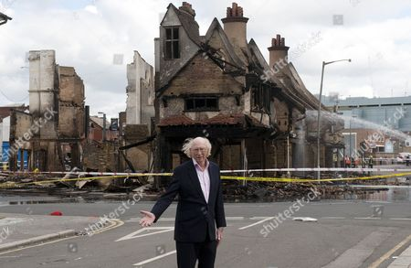 Maurice Reeves, Chairman of Reeves Furniture store in front of the burnt out shop.