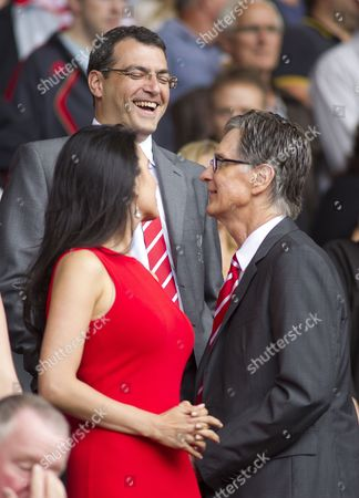 Liverpool Director of Football Damien Comolli shares a joke with club owner John W Henry and his wife Linda Pizzuti