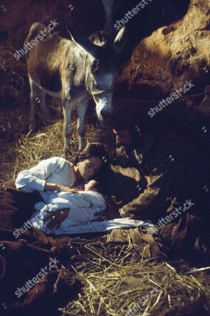 (l-r) Olivia Hussey as Mary, the mother of Jesus, unknown as baby Jesus, Yorgo Voyagis as Joseph