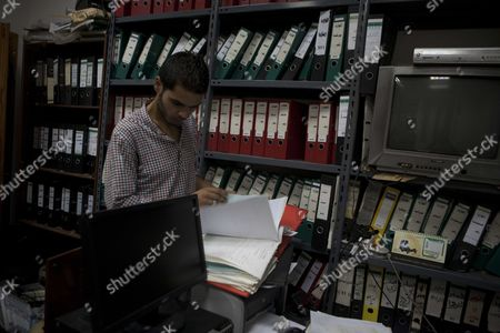 A Libyan guard looking at secret intelligence in an office of right hand man of Gaddafi, Moussa Koussa, Libya's foreign intelligence chief   in Tripoli