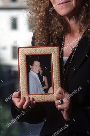 Edie Lutnick holding a photo of her brother Gary Lutnick