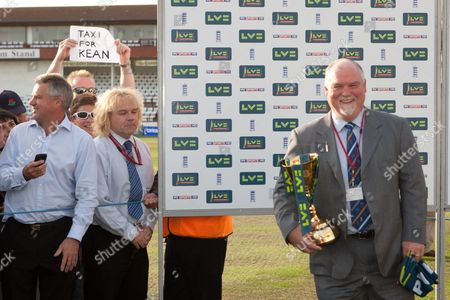 As former England captain Mike Gatting waits to present the trophy, a Lancashire fan (l) holds a sign saying 'Taxi for Kean'