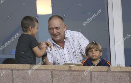 Cruz Beckham arm wrestles his granddad Ted Beckham as Romeo Beckham  watches the match