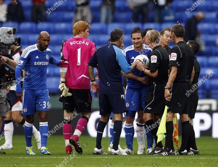 Frank Lampard of Chelsea receives the matchball from Referee Mr Peter Walton at the end of Game next to Bolton Wanderers manager Owen Coyle