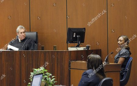 Judge Michael E. Pastor listens as Sade Anding gives evidence