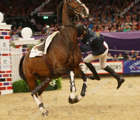 Stock Photo of Tina Fletcher (GBR) falling off her horse in The Tagg Puissance jumping 7 ft 3 ins