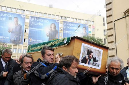 The coffin bearing the late Turkish photojournalist Goksin Sipahioglu is carried through the streets