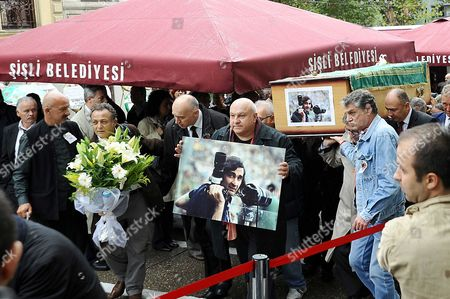 Stock Image of The coffin bearing the late Turkish photojournalist Goksin Sipahioglu is carried through the streets