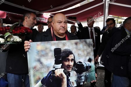 Stock Picture of Mourner with photograph of Goksin Sipahioglu