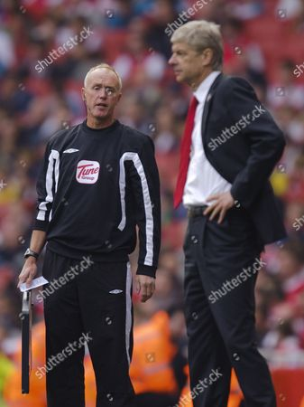 Fourth official Peter Walton tries to explain the amount of added time to Arsenal Manager Arsene Wenger