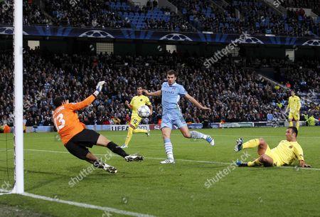 Carlos Marchena of Villarreal scores an own goal under pressure from Edin Dzeko of Manchester City to make it 1-1