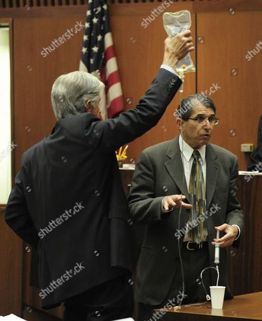 Anesthesiologist and propofol expert Dr. Paul White demonstrates an IV drip with the assistance of defence attorney J. Michael Flanagan (L)