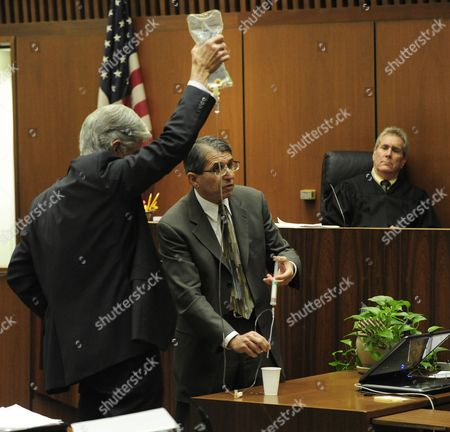 Anesthesiologist and propofol expert Dr. Paul White demonstrates an IV drip with the assistance of defence attorney J. Michael Flanagan as Judge Michael E. Pastor looks on