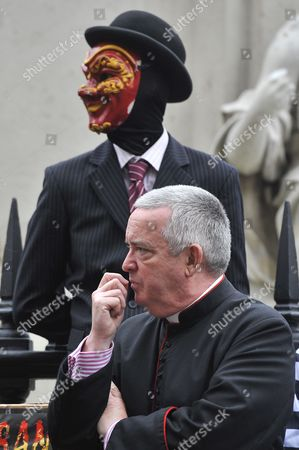 Right Reverend Graeme Knowles the Dean of St Paul's Cathedral with a protester dressed as a banker