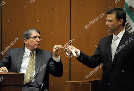 Dr. Paul White examines evidence presented to him by Los Angeles Deputy District Attorney David Walgren