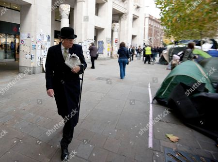 Maxwell Hutchinson dressed in a bowler hat and suit passes the Occupy London protests