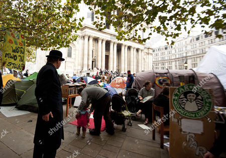 Maxwell Hutchinson dressed in a bowler hat and suit at the camp outside St Paul's Cathedral