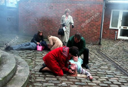 Stock Photo of Iain Rogerson (Harry Flagg)and Hayley Cropper Julie Hesmondhalgh] tends to an unconscious Vicky Entwistle (Janice Battersby) after she is dragged from the factory. Samia Smith (Maria Sutherland) and Helen Worth (Gail Platt) look after Adam Rickitt (Nick Tilsley). Sue Nicholls (Audrey Roberts) looks on concerned.