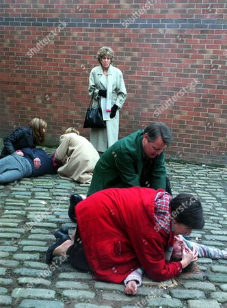 Iain Rogerson (Harry Flagg)and Julie Hesmondhalgh (Hayley Cropper) tend to an unconscious Vicky Entwistle (Janice Battersby) after she is dragged from the factory. Samia Smith (Maria Sutherland) and Helen Worth (Gail Platt) look after Adam Rickitt (Nick Tilsley). Sue Nicholls (Audrey Roberts)looks on concerned.
