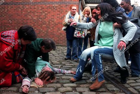 Iain Rogerson (Harry Flagg) and Hayley Cropper Julie Hesmondhalgh] tends to an unconscious Vicky Entwistle (Janice Battersby) after she is dragged from the factory. The factory girls with Jennie McAlpine (Fiz Brown) (left) and Suranne Jones (Karen McDonald) (right) are very upset.