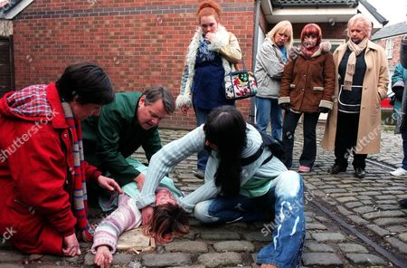 Stock Image of Iain Rogerson (Harry Flagg), Julie Hesmondhalgh (Hayley Cropper) and Suranne Jones (Karen McDonald) tend to an unconscious Vicky Entwistle (Janice Battersby) after she is dragged from the factory. The factory girls with Jennie McAlpine (Fiz Brown) (left) look on concerned