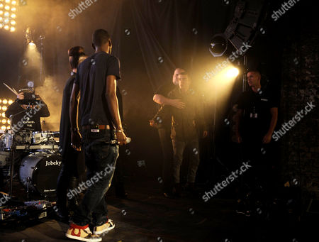 Jonny Clarke, as Bart, rushes the stage while Wretch 32 performs